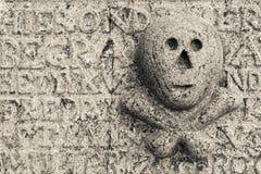 头骨和骨头在墓碑 库存照片