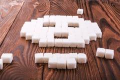 头骨标志由糖立方体制成 糖片断在木背景的 糖瘾概念 不健康的成份 库存照片