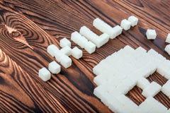 头骨标志由糖立方体制成 糖片断在木背景的 糖瘾概念 不健康的成份 免版税库存照片