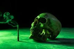 骨骼的抽象静物画头骨有灼烧的香烟的, 免版税库存图片
