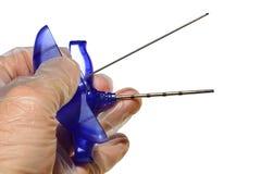 骨髓切片检查法针在两部分,管和针中spliteed,举行在一位医生的左手不育的乳汁手套的,白色后面 库存照片