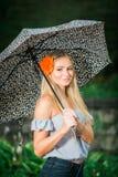 高三学生摆在与画象的伞在多雨 免版税图库摄影