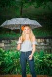 高三学生摆在与画象的伞在多雨 免版税库存图片