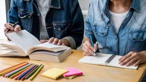 高中坐在书桌的家庭教师或大学生小组在读的图书馆里学习和,做家庭作业和教训实践 免版税库存照片