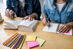高中坐在书桌的家庭教师或大学生小组在读的图书馆里学习和,做家庭作业和教训实践 库存照片
