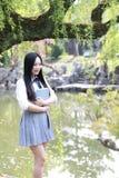 高中大学生享受业余时间的愉快的逗人喜爱的可爱的美丽的女孩由一个湖读了一本书在夏天公园 库存图片