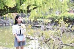 高中大学生享受业余时间的愉快的逗人喜爱的可爱的美丽的女孩由一个湖读了一本书在夏天公园 免版税库存图片