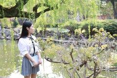高中大学生享受业余时间的愉快的逗人喜爱的可爱的美丽的女孩由一个湖读了一本书在夏天公园 免版税库存照片
