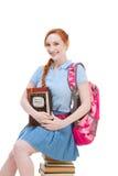 高中女小学生学生坐堆书 免版税库存图片