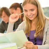 高中学员在图书馆研究中的采取附注 免版税库存照片