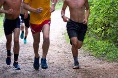 高中男孩运行在道路的越野赛跑者 库存照片