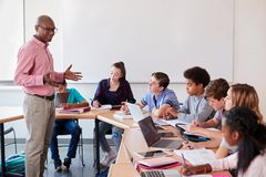 高中老师谈话与使用数字式设备的学生在技术类 免版税库存照片