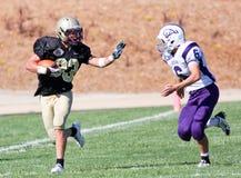 高中跑与球的足球运动员在比赛期间 库存照片