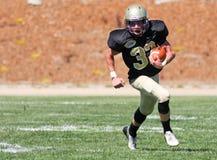 高中跑与球的足球运动员在比赛期间 免版税库存图片