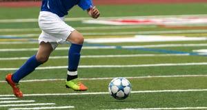 高中跑与球的足球运动员 免版税库存照片