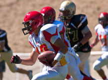 高中跑与球的足球运动员 免版税图库摄影