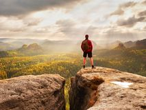 高人享受在山边缘峰顶的自由  单独旅游观看在有薄雾的谷 免版税库存照片