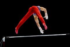 高低杠的体操运动员 免版税库存图片