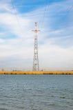 高信赖输电线站立在一条宽广的河边缘 免版税库存图片