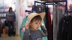 高兴一个的小男孩尝试在一个帽子在商店和 股票视频