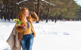 高兴卷发的妇女有步行通过与她的外套的随风飘飞的雪在肩膀 图库摄影