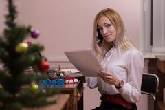 高兴女性工作在圣诞节的一个办公室 免版税库存图片