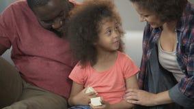 高兴小女孩打开小礼物并且感谢爱恋的母亲和父亲 股票录像