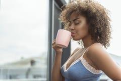 高兴的女孩饮用的杯子液体 免版税图库摄影