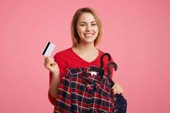 高兴的正面女性拿着在挂衣架的衣裳,并且塑料卡片,去支付新的购买,享受去的购物与最佳的星期五 免版税库存照片