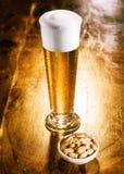 高典雅的杯与坚果的啤酒 免版税库存照片