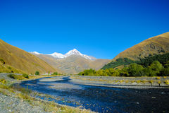 高加索山脉在夏天、高峰Mkinvari和山河 从村庄Sno的看法 免版税库存图片