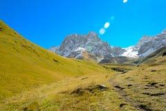 高加索山脉在夏天、绿草、蓝天和雪在高峰Chiukhebi 免版税库存照片