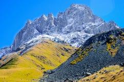 高加索山脉在夏天,绿色山、多雪的山峰Chiukhebi和蓝天 库存照片