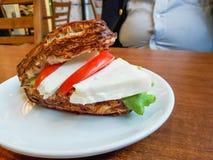 高卡路里食物 苏打面包蕃茄和乳酪三明治与腹部油脂人 库存照片