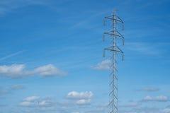高压塔和缆绳在乡下排行在蓝天下 免版税库存照片