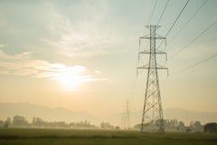 高压杆在早上和阳光 库存图片