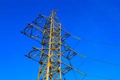 高压电定向塔和传输输电线在蓝天背景 免版税库存照片