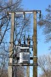 高压电源变压器在两根具体杆登上了在森林-春天 免版税库存照片