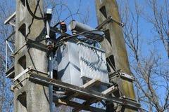 高压电源变压器细节在两根具体杆登上了在森林-春天 免版税库存照片