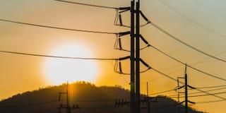 高压电源杆和线剪影 免版税库存照片