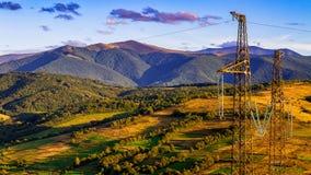 高压线和和力量定向塔在喀尔巴阡山脉的秋天 库存照片