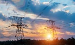 高压输电在日落天空背景中耸立 图库摄影