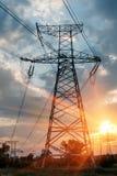 高压输电在日落天空背景中耸立 免版税库存图片