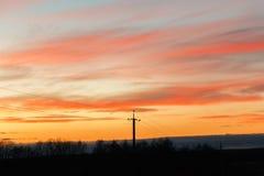 高压输电线剪影以剧烈的天空为背景的在日落 库存照片