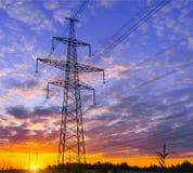 高压输电线剪影反对剧烈和五颜六色的天空的在日出或日落 库存图片