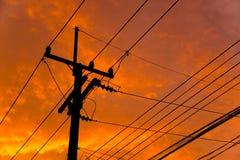 高压输电线剪影反对橙色五颜六色的天空的 免版税库存照片