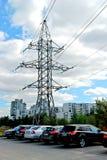 高压输电线和房子在城市 免版税库存图片