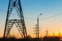 高压输电线在日落背景的一个城市环境里  库存照片