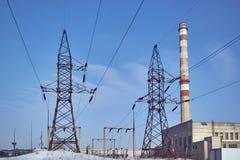 高压输电线支持和一个管子热电站 免版税库存图片
