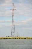 高压输电线横渡水身体 免版税库存照片